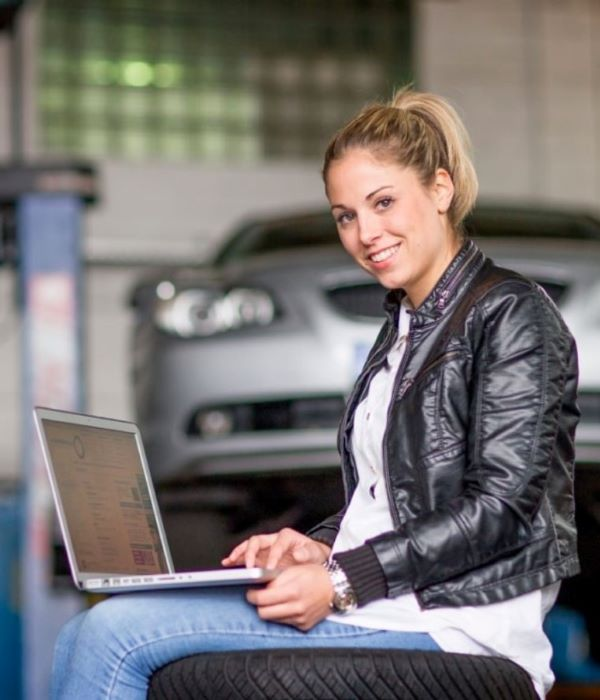 Attractive lady on laptop by car